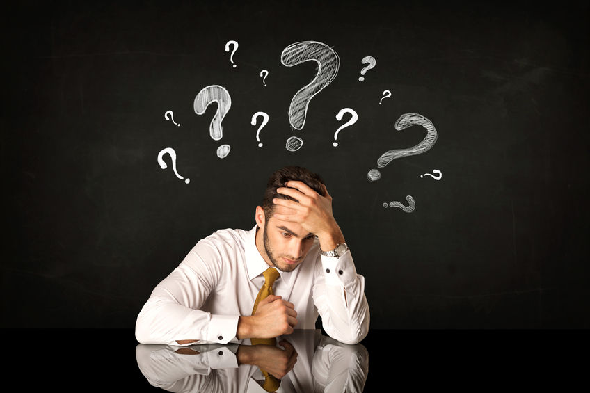40355395 - depressed businessman sitting under question marks
