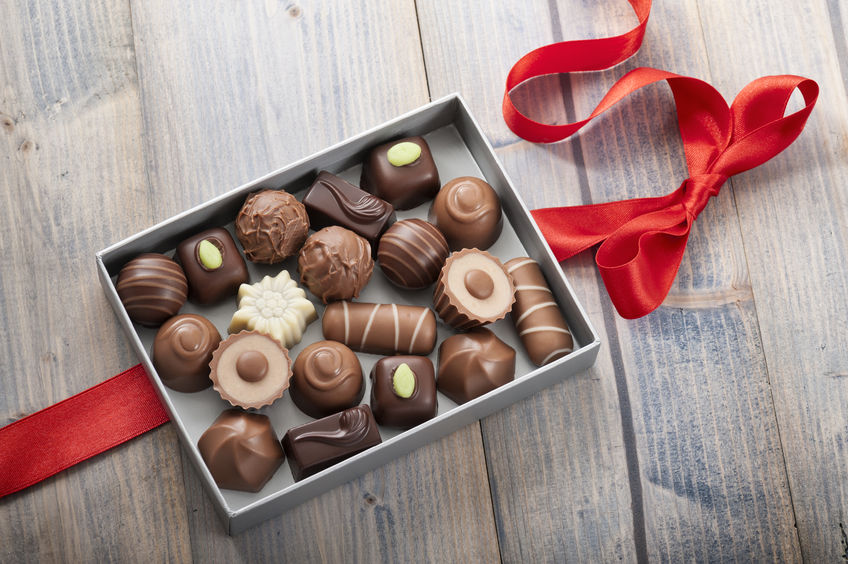 28068104 - assorted chocolates confectionery in their gift box with red bow